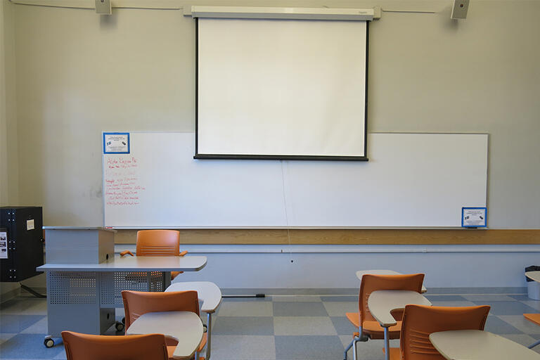 Photo Cory 237 Classroom, audience view, projector screen and whiteboard