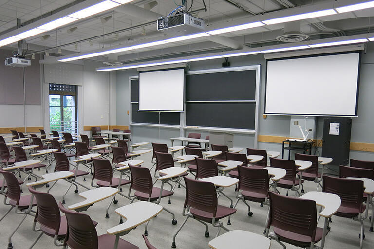 Etcheverry 3106 has 75 movable desks with a moveable speaker podium facing the class. The AV rack/blackbox is in the front of the classroom near the four-panel blackboard near the moveable Document Camera. There are two projector screens, one of which tha
