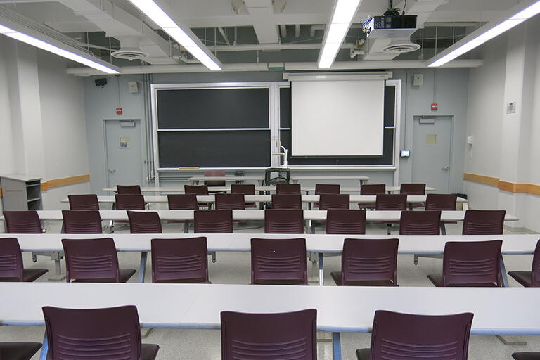 Etcheverry 3109 has five rows of connected desks and fixed chairs with a movable speaker podium. The moveable document camera is in the front of the classroom. The AV rack/blackbox is in the back of the classroom. There is one projector screen that covers