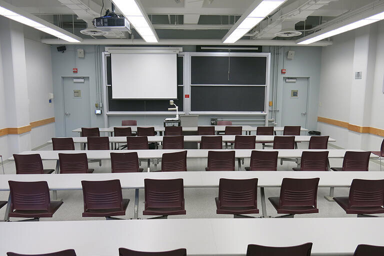 Etcheverry 3113 has five rows of connected desks and fixed chairs with a moveable speaker podium. The moveable document camera is in the front of the classroom. The AV rack/blackbox is in the back of the classroom. There is one projector screen that cover